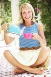 Hällande kopp för hög kvinna av Tea Fotografering för Bildbyråer
