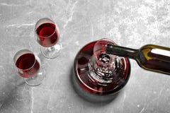 Hällande läckert rött vin in i karaffen på grå färgtabellen, arkivbild