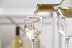 Hällande läckert vitt vin in i exponeringsglas royaltyfri foto