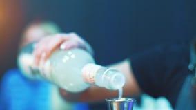 Hällande likör för bartender in i grej under framställning av coctailen Bartenderutrustning lager videofilmer