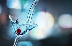 Hällande Martini coctail i exponeringsglas på suddigt fotografering för bildbyråer