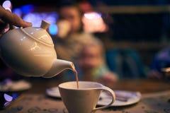 Hällande Masala mjölkar te in i en kopp arkivbilder