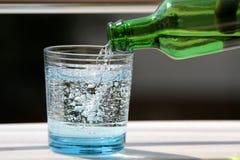 Hällande mineralvatten i exponeringsglaset Arkivbilder