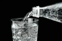 Hällande mineralvatten i exponeringsglaset Arkivfoton