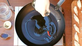 Hällande olivolja över en panna Arkivfoton
