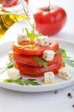 Hällande olivolja över sallad med nötkötttomater och feta Royaltyfria Bilder
