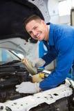 Hällande olja för mekaniker in i bilen arkivbilder