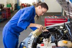 Hällande olja för mekaniker in i bilen royaltyfri foto