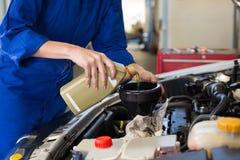 Hällande olja för mekaniker in i bilen arkivbild