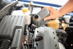 Hällande olja för mekaniker in i bilmotorn royaltyfri fotografi