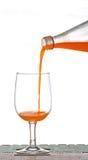 Hällande orange fruktsaft från flaskan in i exponeringsglas Arkivfoto