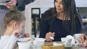 Hällande ost för gullig liten flicka i hennes spagetti i italiensk restaurang, medan hennes unga föräldrar har åt deras grönsak arkivfilmer