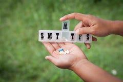 Hällande preventivpillerar för kvinnahand från en preventivpillerpåminnelseask in i hennes hand Royaltyfri Bild