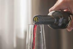 Hällande rött vin för man från flaskan Royaltyfria Foton