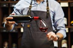 Hällande rött vin för manlig sommelier in i lång-stemmed vinglas Royaltyfri Foto
