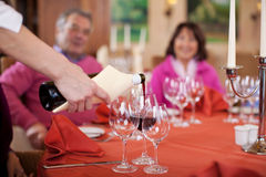 Hällande rött vin för servitris på gästs exponeringsglas Arkivfoton