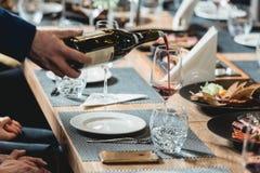 Hällande rött vin för Sommelier in i exponeringsglas på vinavsmakning Arkivbilder