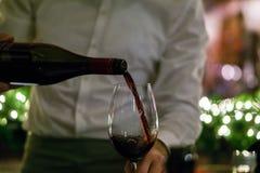 Hällande rött vin för uppassare i ett exponeringsglas royaltyfri foto