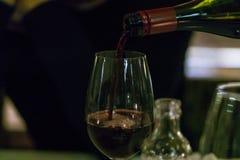Hällande rött vin för uppassare i ett exponeringsglas fotografering för bildbyråer