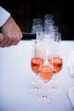 Hällande rött vin för uppassare in i exponeringsglas Royaltyfri Fotografi