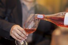Hällande rött vin för uppassare in i exponeringsglas Arkivfoto