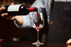 Hällande rött vin för uppassare in i vinglaset Sommelieren häller alkoholdrycken Arkivbild