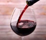 Hällande rött vin in i exponeringsglas Arkivbild