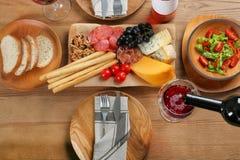 Hällande rött vin in i exponeringsglas på tabellen med läcker mat royaltyfria bilder