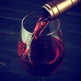 Hällande rött vin in i exponeringsglaset mot träbakgrund Arkivfoto