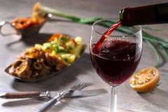 Hällande rött vin och mat Arkivbilder