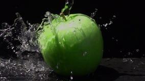 Hällande sötvatten på ett grönt äpple på svart bakgrund lager videofilmer