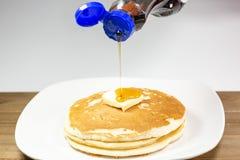 Hällande sirap från en blå spetsflaska på fyrkanten av smör på en bunt av guld- pannkakor som väntar för att ätas royaltyfria bilder