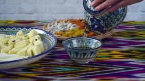 Hällande te för kvinna från den keramiska tekannan för traditionell uzbek, hdvideo lager videofilmer