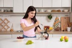 Hällande te för kvinna in i kokkärlet Fotografering för Bildbyråer