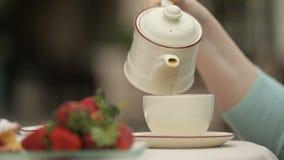 Hällande te för kvinna i koppen som kopplar av i utomhus- kafé, jordgubbeplatta på tabellen arkivfilmer
