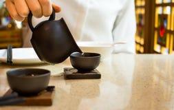 Hällande te för kvinnlig in i den keramiska tekoppen arkivbild
