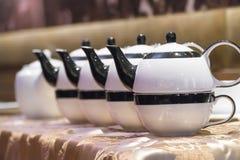 Hällande te för tekanna in i en kopp på en wood yttersida Arkivbilder