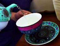 hällande te för tekanna in i en tekopp Royaltyfria Foton