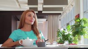 Hällande te för ursnygg lycklig kvinna i hennes kopp som tycker om frukosten på restaurangen stock video