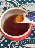 Hällande te in i en röd kopp Arkivfoto