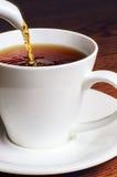 Hällande te in i en vit kopp Arkivfoto
