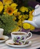 hällande teapot för kopp Arkivbild