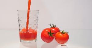 Hällande tomatfruktsaft in i ett exponeringsglas lager videofilmer