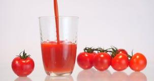 Hällande tomatfruktsaft in i ett exponeringsglas arkivfilmer
