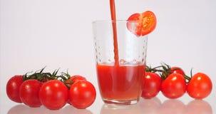 Hällande tomatfruktsaft in i ett exponeringsglas stock video