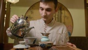 Hällande varmvatten för teförlage från kokkärlet till gaiwan för att brygga te på ceremoni arkivfilmer