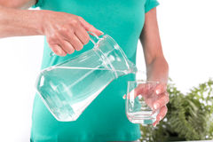 Hällande vatten för kvinna in i ett exponeringsglas Arkivbild