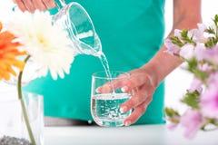 Hällande vatten för kvinna in i ett exponeringsglas Fotografering för Bildbyråer