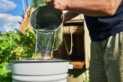 Hällande vatten för man som precis väl tas upp från in i en emaljerad hink arkivfoto