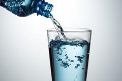 Hällande vatten från flaskan in i exponeringsglas arkivbild